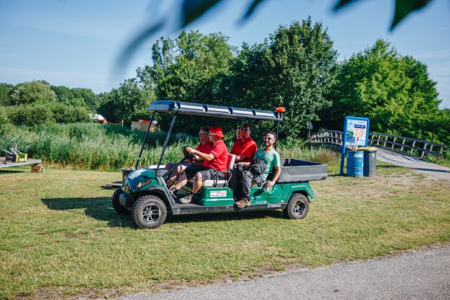 four construction people driving in a golf cart over festival grounds